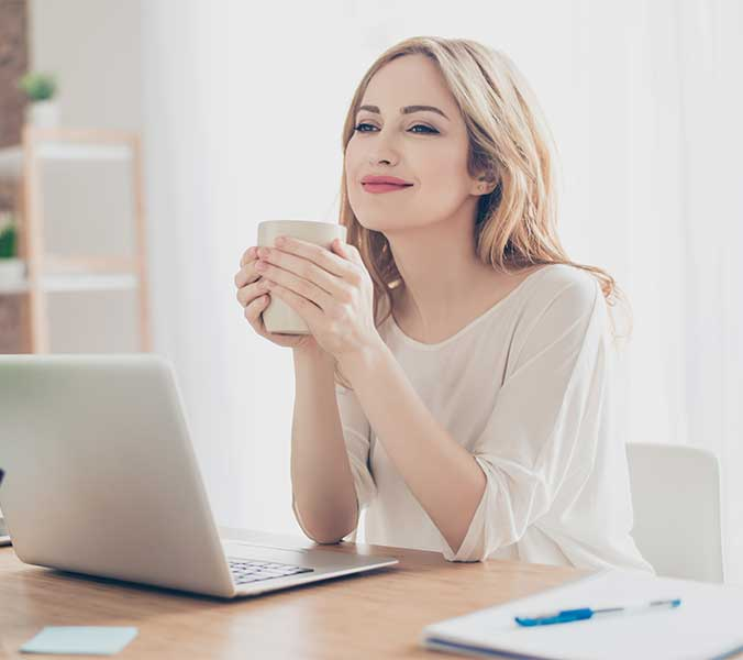 Daydreaming woman sitting at a desk with a laptop while holding a cup.